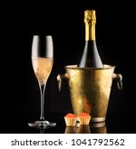 Small photo of Red caviar and champagne in a bottle and a glass on a black background