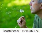 man blowing dandelion over... | Shutterstock . vector #1041882772