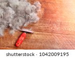 Small photo of Concept Dogs Shed spring shedding grooming season. De shedding tool - rakers brush for Dog. Slicker brushes on floor next to a pile of wool. Copy space.