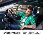 a bearded man in a new car.   Shutterstock . vector #1042094632