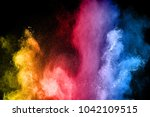 The explosion of multi colored powder. Beautiful rainbow color powder fly away. The cloud of glowing color powder on black background