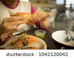 hand of woman peeled grilled... | Shutterstock . vector #1042120042
