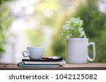 white cup with green plant at... | Shutterstock . vector #1042125082