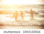 three surfers practicing in the ... | Shutterstock . vector #1042133026