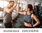 Small photo of A beautiful girl and her well-built boyfriend are greeting each other with a high-five. They are happy to see each othr in the gym. Young people are ready to start their workout.