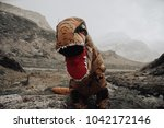 man with dinosaur costume in a... | Shutterstock . vector #1042172146