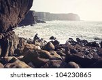 man sits pensively on rock by... | Shutterstock . vector #104230865