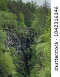 Small photo of Braemore, Scotland - June 8, 2012: Corrieshalloch Gorge, a deep cut in landscape with forested vertical slopes. Suspension bridge over chasm. Focus on black rocks and abundance of green trees.