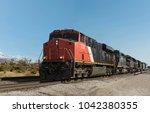 a freight train rolls through... | Shutterstock . vector #1042380355