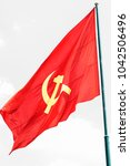 Small photo of Large communist flag floating in the wind with a blue sky background