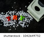Small photo of gray hole puncher on black background with try note and paper pieces. motivation message of keep trying