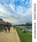 Small photo of KYOTO, JAPAN - SEPTEMBER 12, 2015: Japanese locals having a stroll on the sandy footpath near the riverbank of Kamo River in Kyoto City, while others sit down on the grass patches to unwind and relax