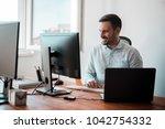 smiling handsome man working in ... | Shutterstock . vector #1042754332