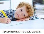 tired little boy sitting at the ... | Shutterstock . vector #1042793416