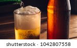 pouring foaming beer into glass ... | Shutterstock . vector #1042807558