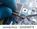 hand with tweezers holding the... | Shutterstock . vector #1042858978