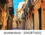 ancient street in siracusa ... | Shutterstock . vector #1042871632