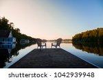 muskoka chairs sitting at the... | Shutterstock . vector #1042939948