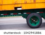 Small photo of Yellow rusty container on flat bed semi trailer with green wheels on green trailer frame driving on the multiline road