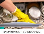 woman puts dishes in the... | Shutterstock . vector #1043009422