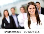 Successful woman leading a business group and smiling - stock photo