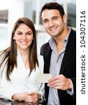 Couple holding a credit or debit card and smiling - stock photo