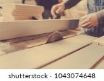 Small photo of A carpenter works on woodworking the machine tool. Toned image. Man collects furniture boxes. Saws furniture details with bare saw blade view