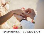 groom wears ring on bride's... | Shutterstock . vector #1043091775