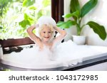 little child taking bubble bath ... | Shutterstock . vector #1043172985