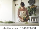 young female florist putting... | Shutterstock . vector #1043374438