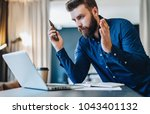 young bearded businessman sits... | Shutterstock . vector #1043401132