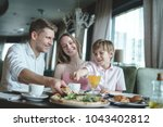 young family having lunch in a... | Shutterstock . vector #1043402812