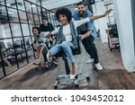 office fun. four young cheerful ... | Shutterstock . vector #1043452012
