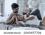 Small photo of Simple joy of loving. Attractive young people lying on the bed and smiling while spending free time at home