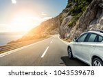 Stock photo white car rushing along a high speed highway toned photo 1043539678