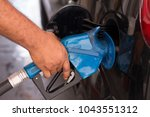 hand holding pumping gasoline... | Shutterstock . vector #1043551312