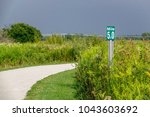 Small photo of Mile marker along trail of crushed limestone through prairie restoration area late in summer, northern Illinois, USA, with stormy sky in background (5 miles equals 8 kilometers) (selective focus)