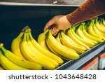 mans hand take bananas from... | Shutterstock . vector #1043648428