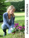 Cheerful Blond Woman Planting...