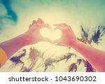 hands in heart shape framing... | Shutterstock . vector #1043690302