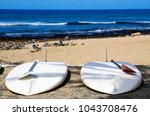 paddle boards on the beach of... | Shutterstock . vector #1043708476