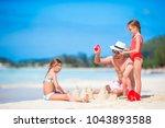 family making sand castle at... | Shutterstock . vector #1043893588