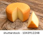 Cheese Wheel On Wooden Table