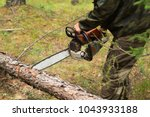 man cuts tree with chainsaw in ... | Shutterstock . vector #1043933188