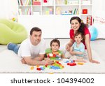 Family time - young parents with two kids playing together at home - stock photo