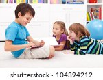 Kids reading funny story at home - smiling happily - stock photo