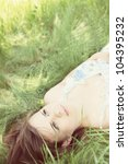Dreamy woman lies supine on the grass - stock photo