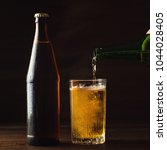 pouring foaming beer into glass ... | Shutterstock . vector #1044028405