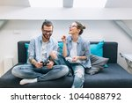 young couple playing video... | Shutterstock . vector #1044088792
