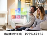 a couple sitting on the sofa... | Shutterstock . vector #1044169642